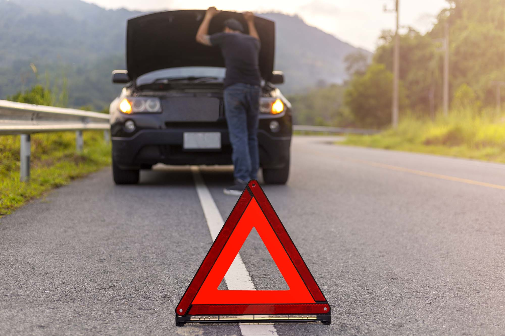 Breakdown Recovery sign with man looking at car engine